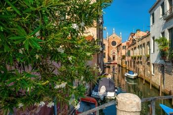 Paddle Board on the Brazzo Canal, in front of the Madonna de l'Orto Church, in the Cannaregio District in Venice.