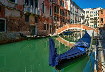 Gondolas on the San Severo Canal in front of the Novo Bridge, on the left after the bridge is the Grimani Palace, in the Castello District in Venice.