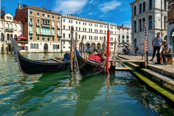 Gondolas on Venice Grand Canal, in front of the Fondaco dei Tedeschi and the Camerlenghi palace.