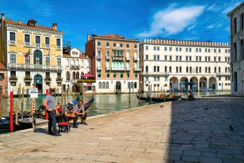 Gondoliers at the Erbaria Square in front of Venice Grand Canal, in the background, the Fondaco dei Tedeschi.