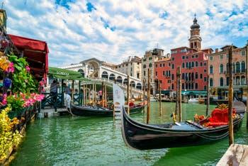 Gondolas and gondoliers on Venice Grand Canal, in front of the Rialto Bridge.