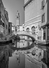 Fenice Bridge on de le Veste Canal and Santo Stefano Bell Tower in Saint Mark in Venice.